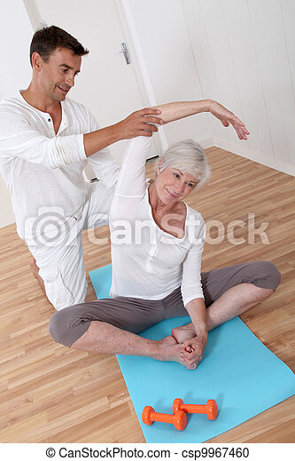 Sport coach training senior woman with stretching exercises - csp9967460