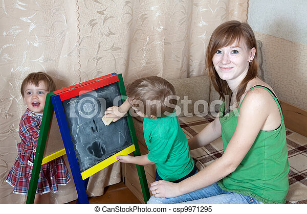 Woman and children draws on blackboard