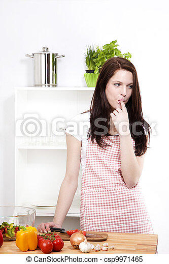 young woman wearing a apron in her kitchen sucking her finger - csp9971465