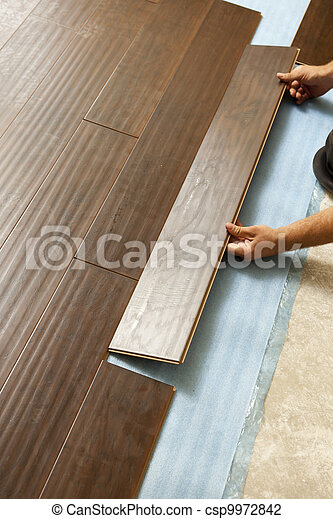 Man Installing New Laminate Wood Flooring - csp9972842