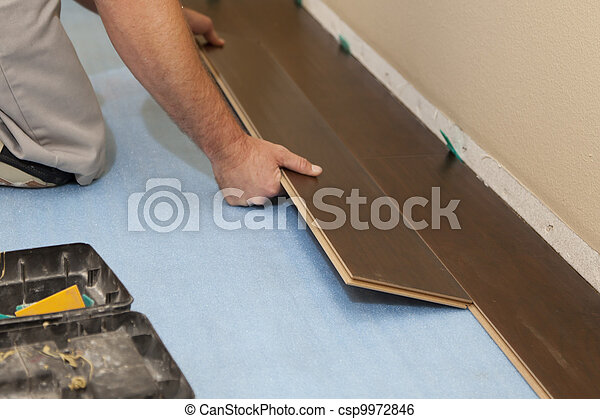 Man Installing New Laminate Wood Flooring - csp9972846