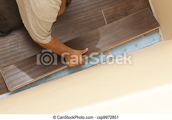 Man Installing New Laminate Wood Flooring - csp9972851