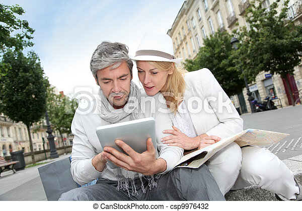 Couple visiting city with help of map and electronic tablet - csp9976432
