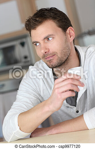 Portrait of handsome guy drinking coffee in home kitchen - csp9977120