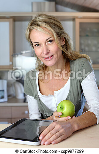 Cheerful adult woman websurfing with tablet and eating apple - csp9977299