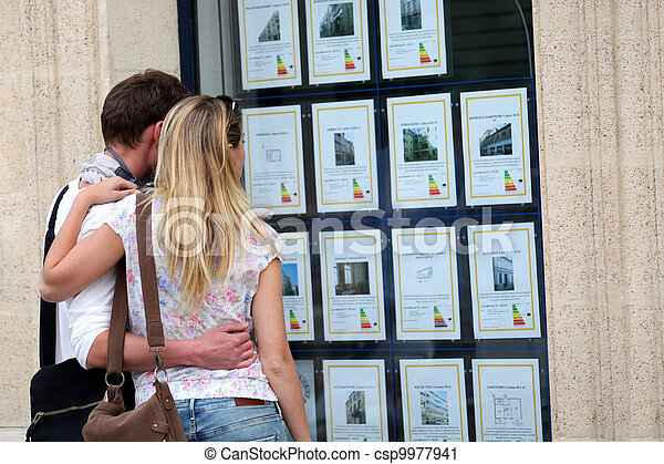 Couple looking at house-for-sale ads through shop window - csp9977941