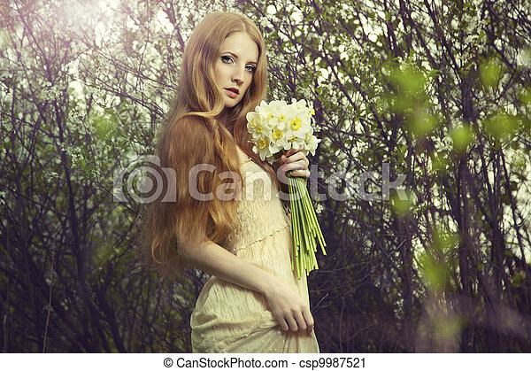 Portrait a beautiful young woman with flowers in the garden - csp9987521