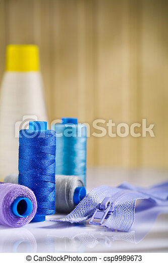 spools and zip on white table - csp9989673