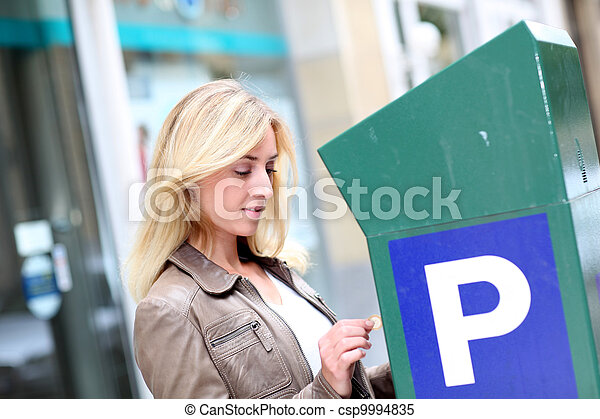 Woman putting coins in parking meter - csp9994835