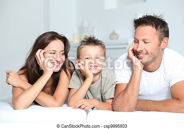 Closeup of parents and child relaxing at home on sofa - csp9995933