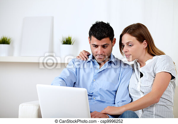 Interested couple browsing on laptop - csp9996252