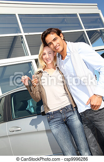 Couple holding car key in automobile dealership - csp9996286