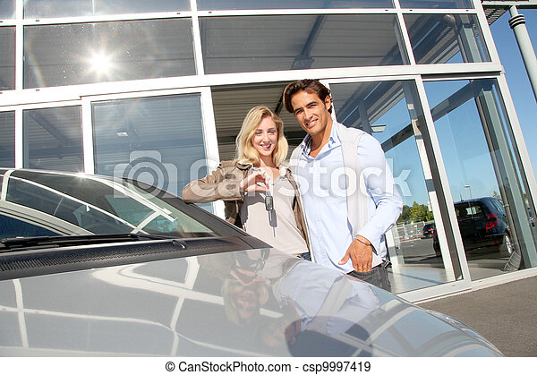 Couple holding car key in automobile dealership - csp9997419