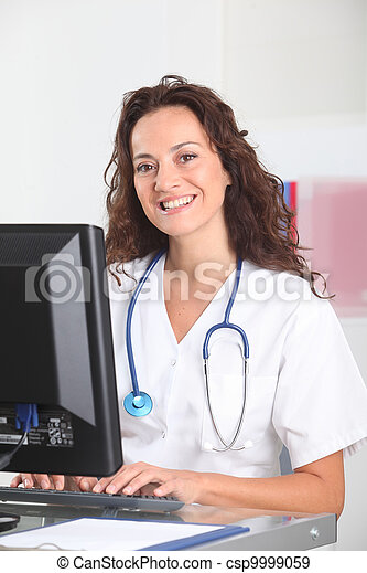 Smiling nurse in front of computer - csp9999059