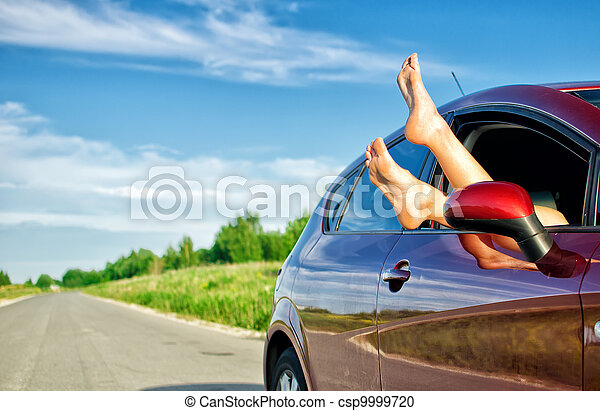 Woman's legs out of the car window. Concept of carefree funny trip. - csp9999720