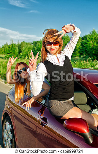 Two pretty happy girls in the car. Concept of carefree roadtrip - csp9999724