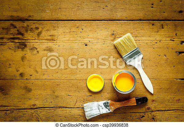 Can with yellow paint and brush on wooden background - csp39936838