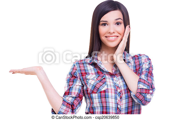 Can you believe it? Surprised young woman holding copy space and touching face with hands while standing isolated on white - csp20639850