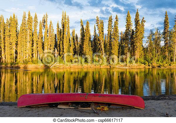 Canoa roja en la orilla del río nisutlin yukon canada - csp66617117