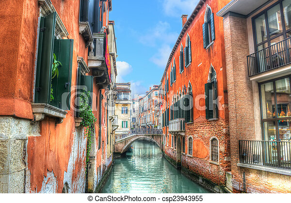 Canal estrecho en Venecia bajo un cielo azul - csp23943955