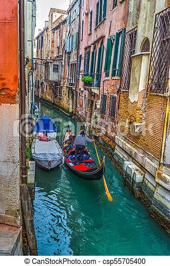 Gondolero en un pequeño canal en Venecia - csp55705400