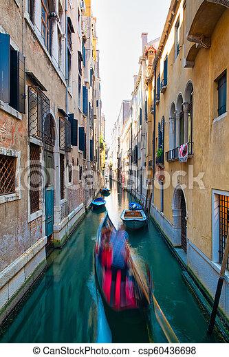 Efecto borroso para un gondolero con turistas en un canal en Venecia - csp60436698