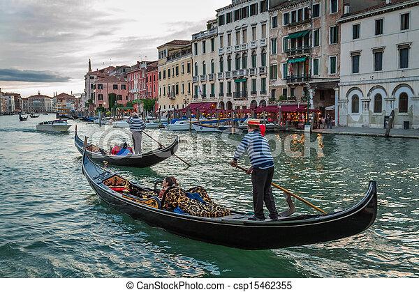 Gondoleros navegando con turistas en el Gran Canal al atardecer en Venecia - csp15462355
