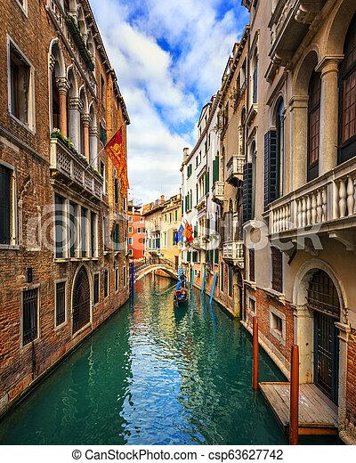 Canal con góndolas en Venecia, Italia. Arquitectura y puntos de referencia de Venecia. Una postal de Venecia con góndolas de Venecia. - csp63627742