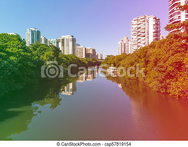 Vista aérea del canal Marapendi en Barra da Tijuca en un día de verano. rascacielos residenciales altos en ambos lados, con vegetación verde. Filtro de filtración de luz de color - csp57819154