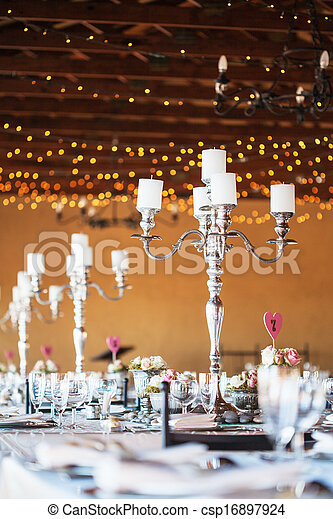 Candelabra with candles on decorated wedding reception tables - csp16897924