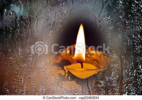 Candle in the rainy window. - csp23463634