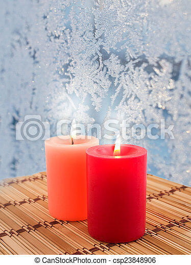 candles burn on a background of frozen window - csp23848906