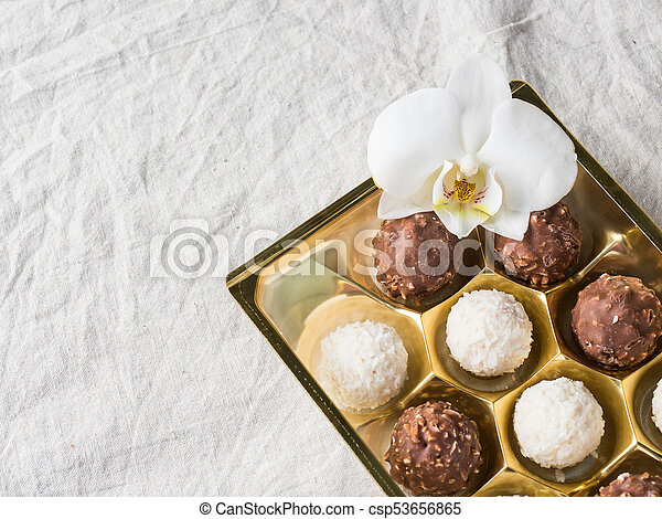 Candy with Coconut in a Gold Box of the Cell on the Table of the Coffee beans Copy space - csp53656865
