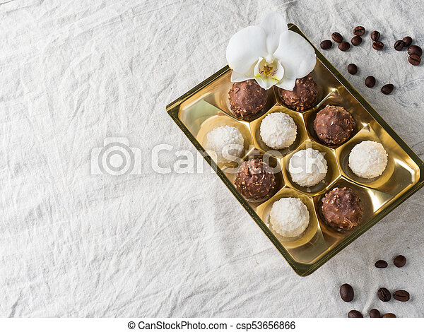 Candy with Coconut in a Gold Box of the Cell on the Table of the Coffee beans Copy space - csp53656866