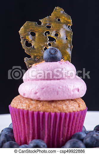 Cannabis oil concentrate aka shatter against over a pink cupcake isolated - csp49922886