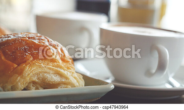 Cappuccino with a French roll for breakfast - csp47943964