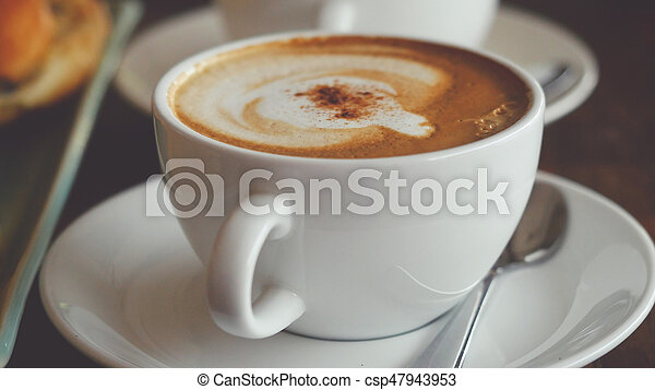 Cappuccino with a French roll for breakfast - csp47943953