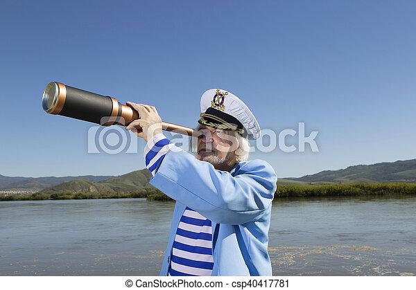 Captain looks through a telescope - csp40417781