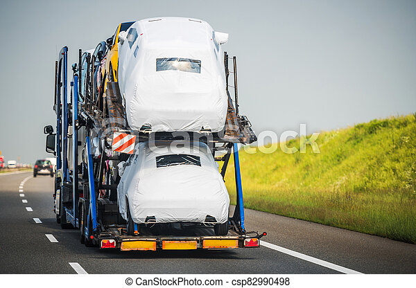 Car Carrier Trailer Full of Vehicles Driving Down the Highway - csp82990498