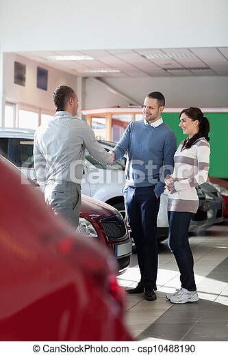 Car dealer shaking hand with a man - csp10488190