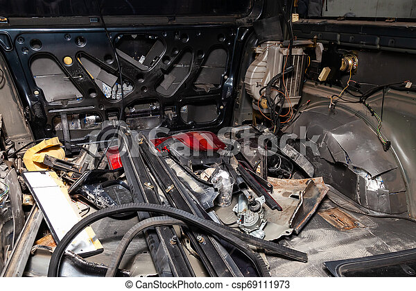 Car interior in the back of a van with a disassembled lining, seats removed, spare parts lying on the floor glass and rubber seal during preparation in a vehicle repair workshop. Auto service industry - csp69111973