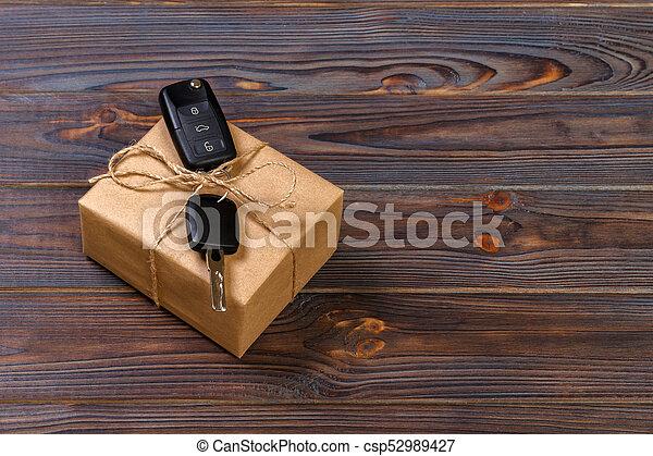 car key and gift box on dark background - csp52989427