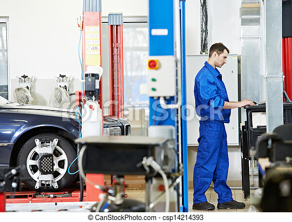car mechanic at wheel alignment with computer - csp14214393