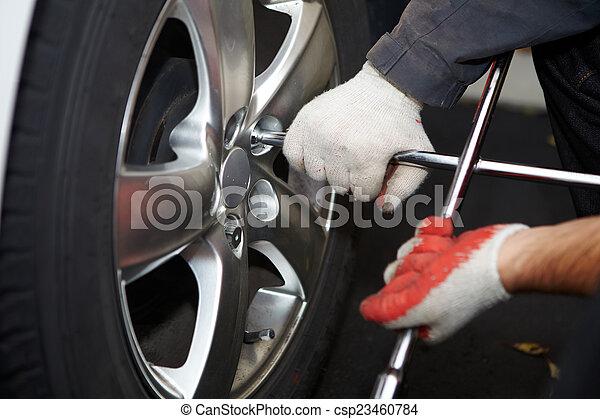 Car mechanic changing tire. - csp23460784