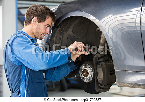 Car Mechanic Examining Brake Disc With Caliper - csp31702587