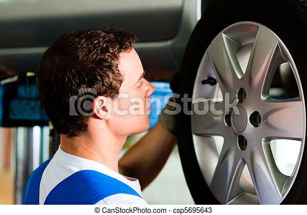Car mechanic in workshop changing tire - csp5695643