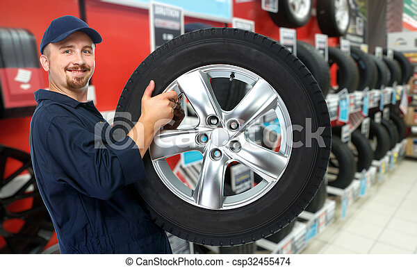 Car mechanic with a tire. - csp32455474