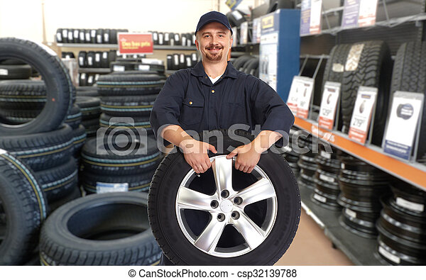 Car mechanic with a tire. - csp32139788