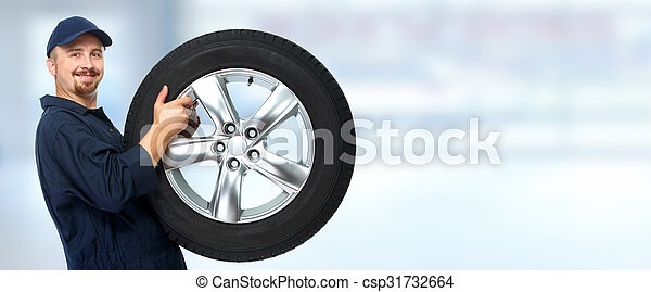 Car mechanic with a tire. - csp31732664