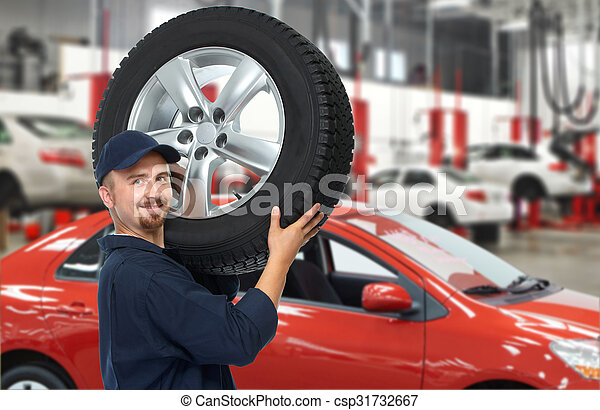 Car mechanic with a tire. - csp31732667